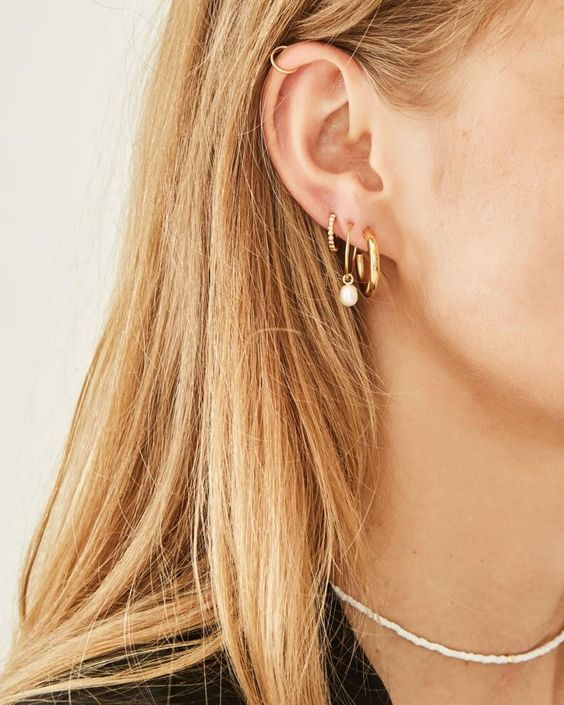 a statement gold hoop, a gold hoop with a pearl and an embellished hoop mini earring