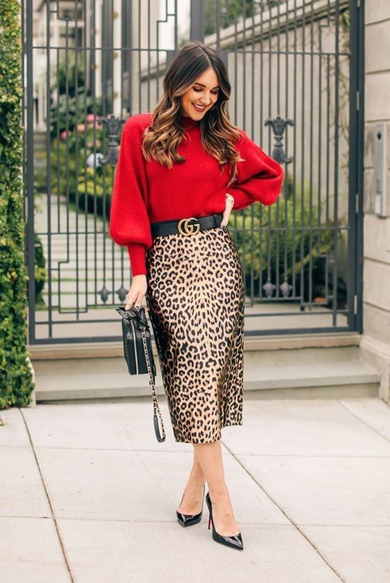 a stylish Christmas party look with a deep red sweater with puff sleeves, a leopard midi skirt, black heels and a black bag