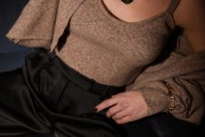 a stylish and chic outfit of black pants, a brown knit top and cardigan, a chain necklace and a matching bracelet
