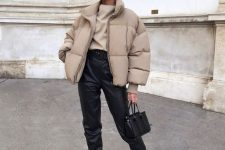 a stylish and laconic look with a tan top, black leather pants, black Chelsea boots and a black bag plus a tan cropped puffer jacket