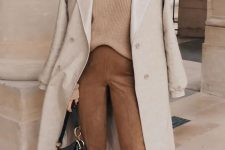 a stylish and simple outfit with a tan sweater, suede brown pants, two tone shoes and a black bag plus a neutral coat