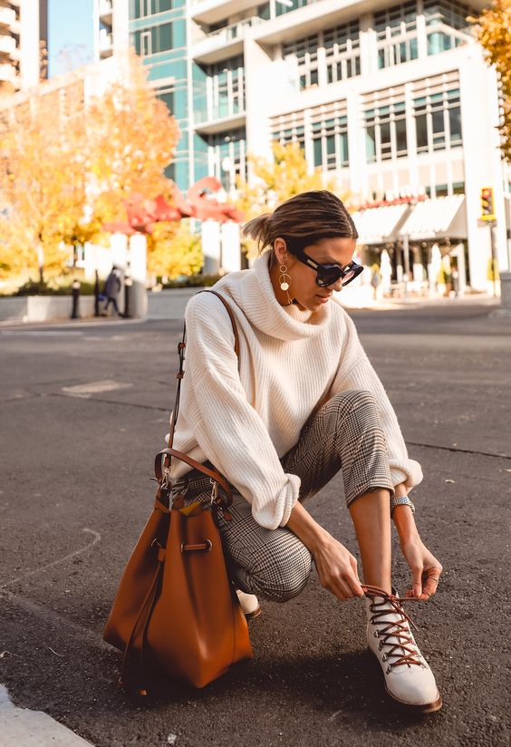 a stylish and simple outfit with an oversized white sweater, plaid pants, white hiking boots and an amber bag