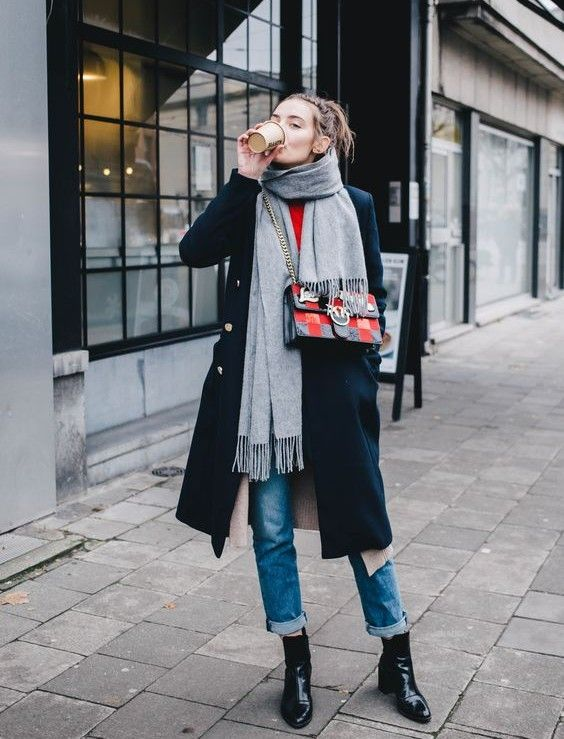 a stylish outfit with a red top, blue jeans, lacquer boots, a black coat and a grey scarf plus a printed bag