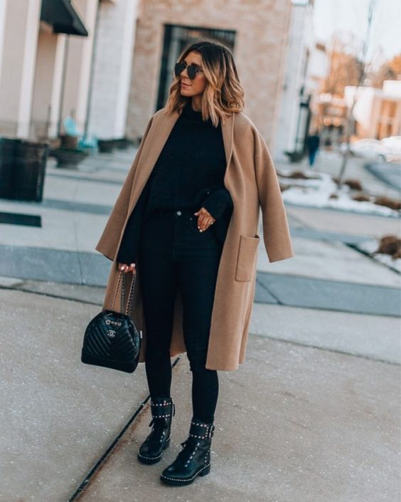a stylish outfit with a sweater, leggings, embellished boots, a bag and a camel midi coat