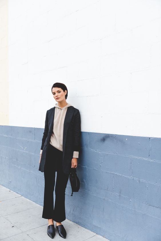 a stylish outfit with a tan cashmere hoodie, an oversized blazer, black flare pants and mules and a small bag