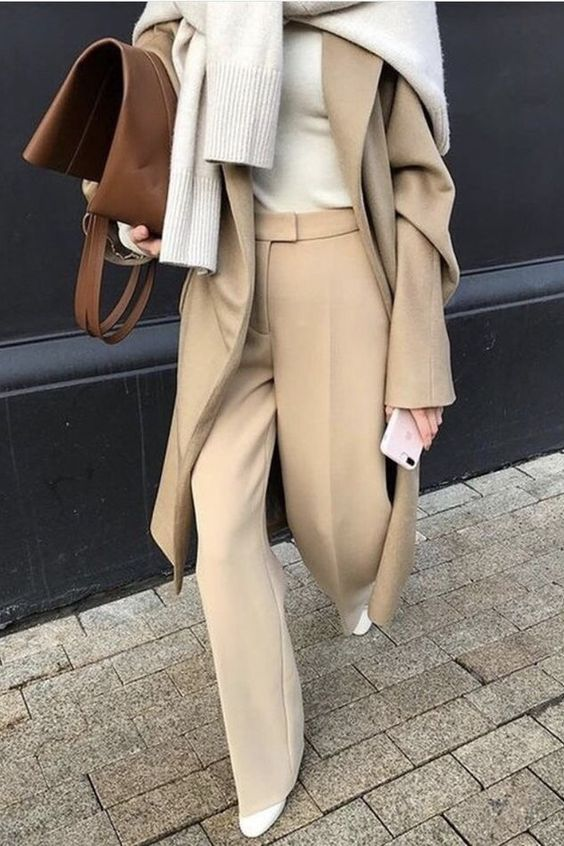 a stylish winter work look with tan pants, white boots, a white turtleneck, a grey sweater and a tan coat plus a brown bag