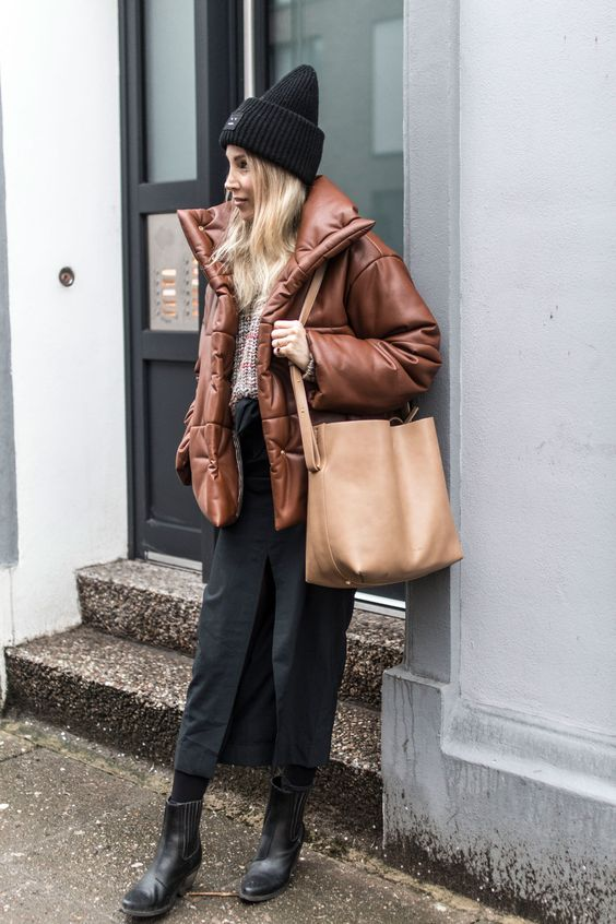 a sweater, a black midi skirt with a slit, black booties,, a brown leather puffer jacket, a black beanie and a tan tote