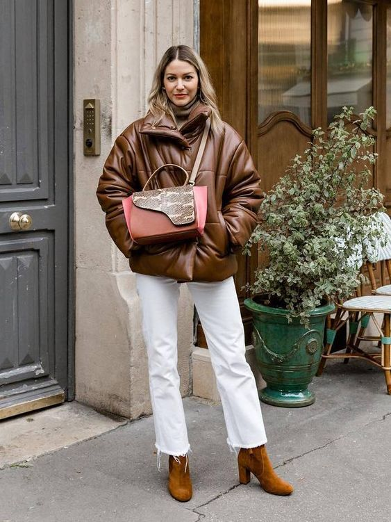 a tan turtleneck, white jeans, mustard suede booties, a brown leather puffer jacket and a bold bag