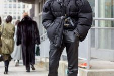 a total black look with a hoodie, leather pants, booties, an oversized short puffer jacket with a leather belt