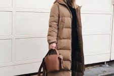 a total black look with a top and pants, a black beanie, an ocher puffer coat, a brown bag and white trainers