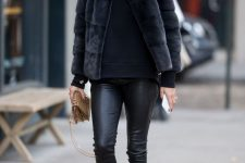 a total black look with leather leggings, boots, a hoodie and a faux fur jacket plus a tan bag