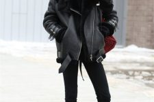a total black look with skinnies, boots, a sweater, an oversized scarf, a shearling coat and a burgundy bag