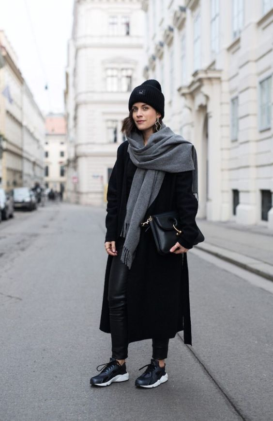 a total black outfit with leather pants, trainers, a coat, a beanie, a bag and an oversized grey scarf