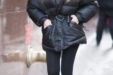 a total black sporty outfit with leggings, white sneakers, a black puffer jacket with a belt and a cap