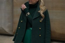 a total green look with a sweater, a metallic pleated midi, a short coat, a round bag and gold touches