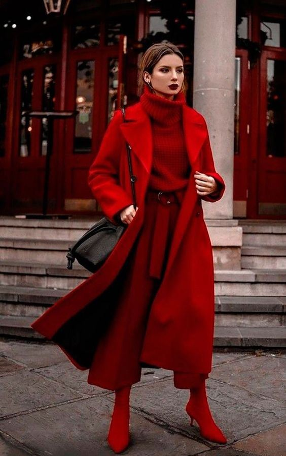 a total red look with a sweater, pants, sock boots, a midi coat and a black bag plus a deep burgundy lip