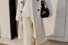 a total white look with an oversized sweater, pants, a midi coat with black buttons, a black bag and boots