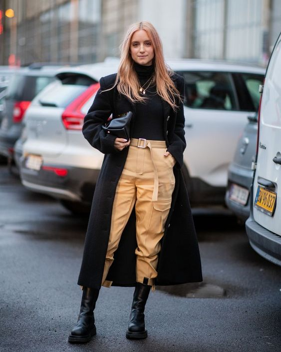 a trendy outfit with a black turtleneck, tan cargo pants, black Chelsea boots, a midi coat and a bag