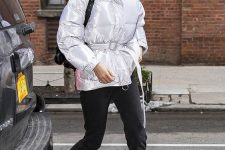 a trendy winter look with a shiny white puffer jacket with a belt, black jeans, combat boots and a black bag