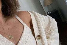 a white knit crop top paired with a matching cardigan and layered necklaces – just add jeans and go