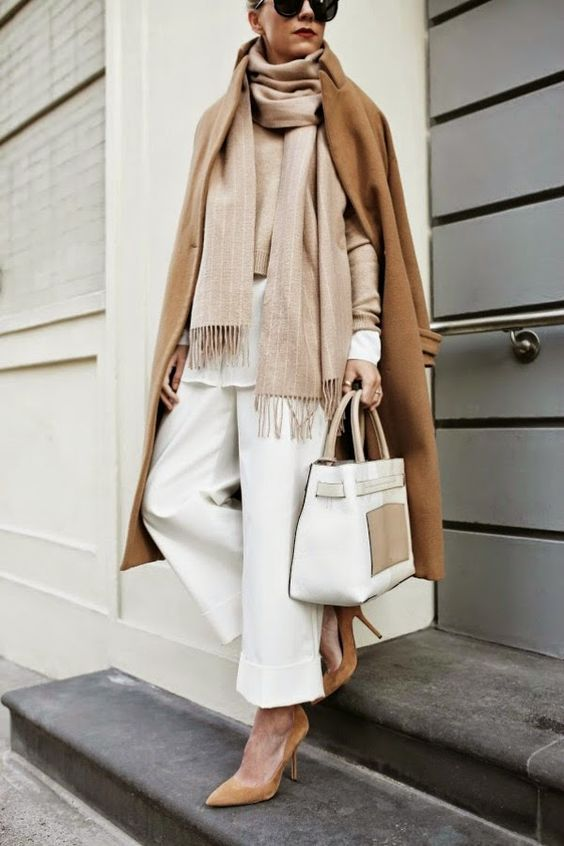 a white shirt, a tan sweater, white pants, tan suede shoes, a tan striped scarf, a camel coat and a white bag