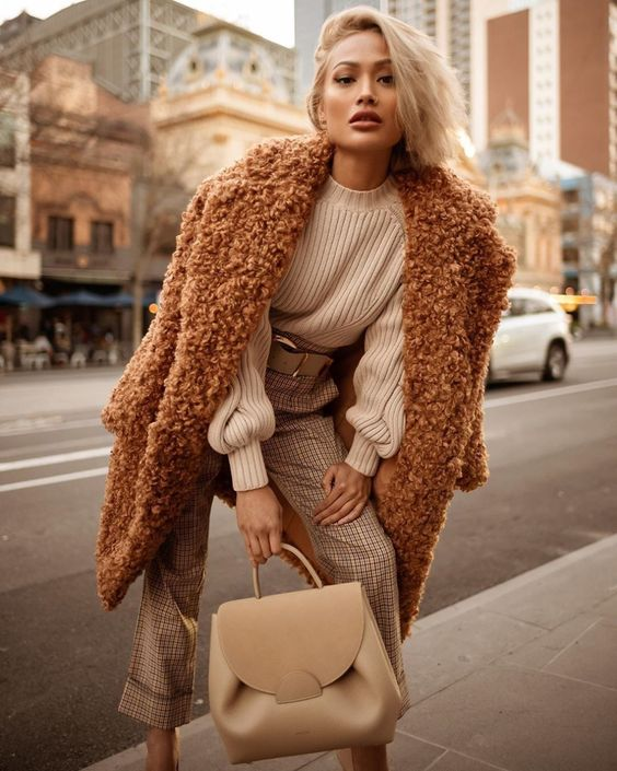 a white sweater, plaid neutral pants, a brown fuzzy faux fur coat and a tan bag for winter