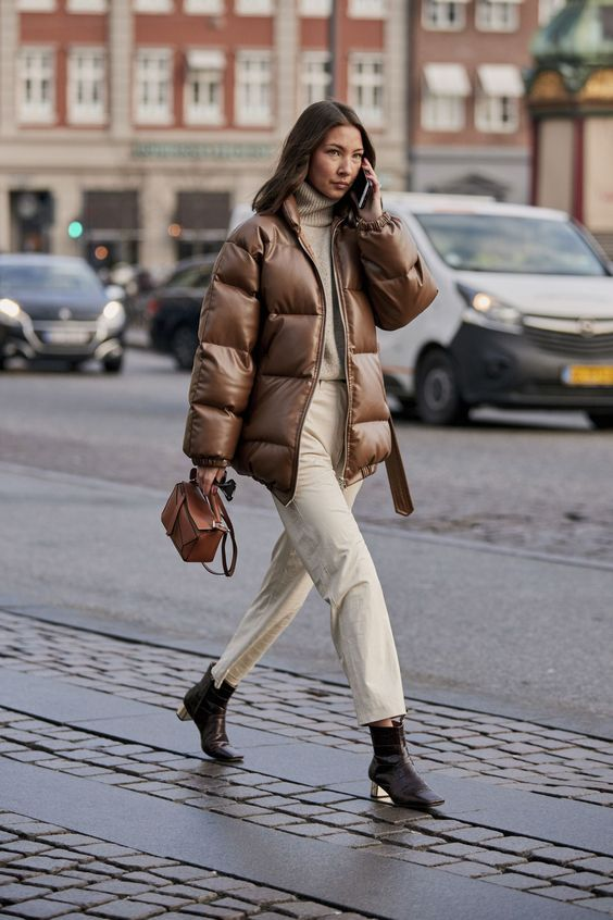 a white sweater, straight jeans, black booties, a brown leather puffer jacket and an amber bag