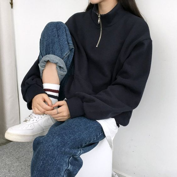 a white tee, a black zip sweater, blue jeans and white sneakers for a cozy and a bit sporty look