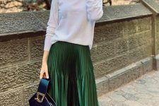 a white turtleneck, a green metallic pleated midi, black boots and a black bucket bag for a feminine feel