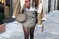 a white turtleneck a wrap mini tweed skirt, black combat boots, a tan and white shearling coat
