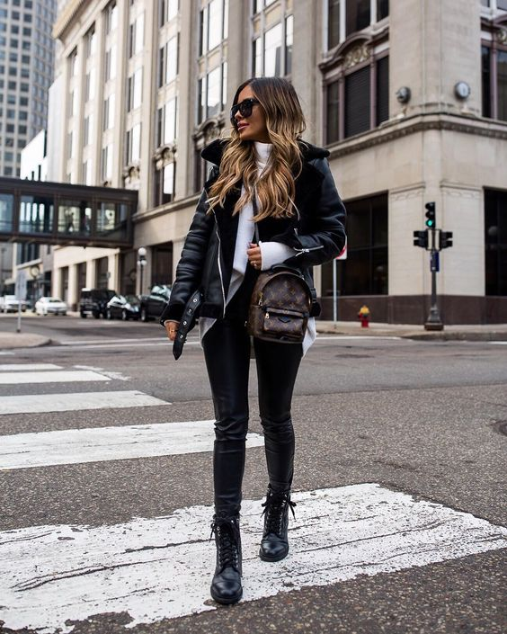 a white turtleneck sweater, black leather leggings, boots, a black shearling coat and a brown backpack