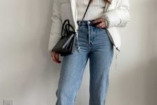 a white turtleneck sweater, blue jeans, black square toe boots, a white puffer jacket and a black bag