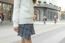 a white turtleneck sweater with braids, a black and grey wrap mini skirt, white booties for a cold winter day