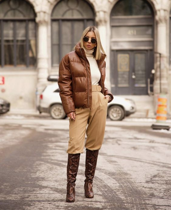 a white turtleneck, tan pants, brown snakeskin print boots, a brown leather puffer jacket for a stylish look