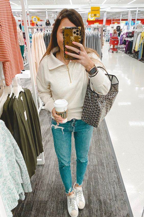 a white zip sweater, blue jeans, white sneakers and a shopper compose a comfy look for every day