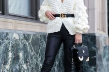 a winter date night outfit with black leather leggings, a white oversized cardigan, a belt, leopard print shoes and a black bag