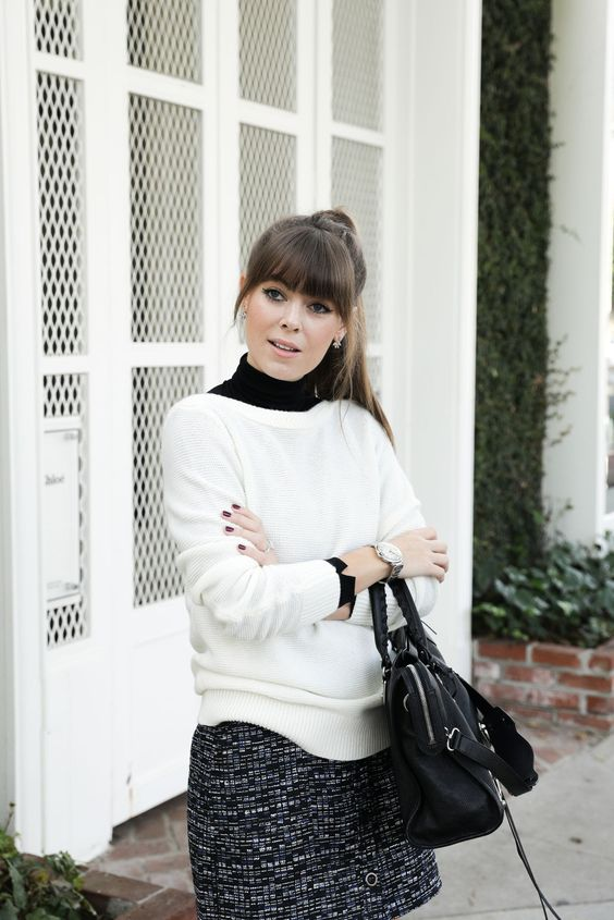 a work outfit with a black turtleneck, a white sweater, a black tweed mini skirt and a black comfy bag