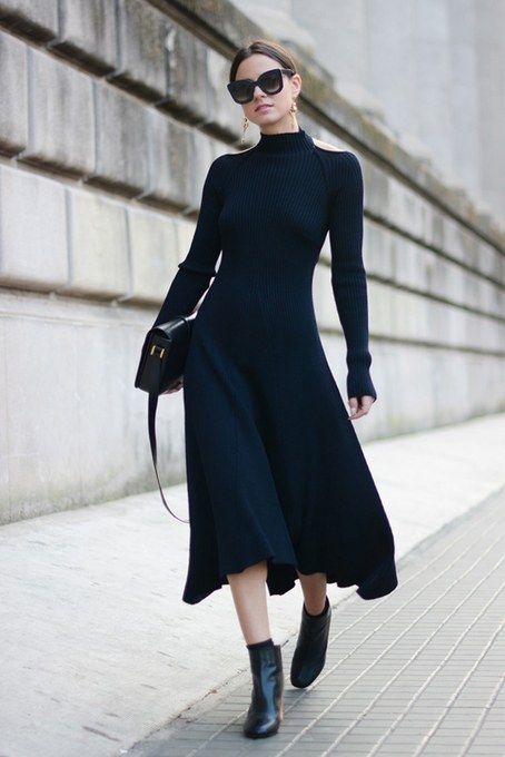 an elegant black A-line midi sweater dress, black booties, a black bag and statement earrings