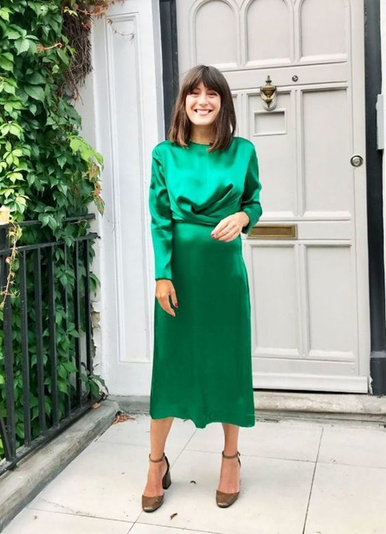 an emerald silk midi dress with a wrapped bodice and long sleeves plus metallic shoes