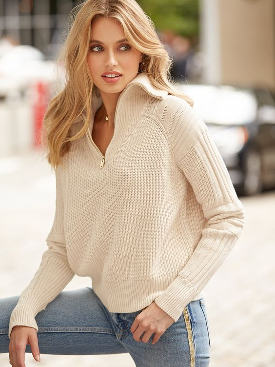 an ivory chunky knit zip sweater and light blue jeans for a chic and trendy look