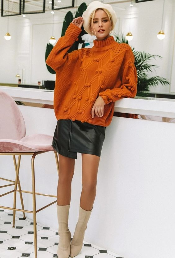 an orange oversized sweater, a black leather asymmetrical mini skirt, ivory sock boots and an ivory beret