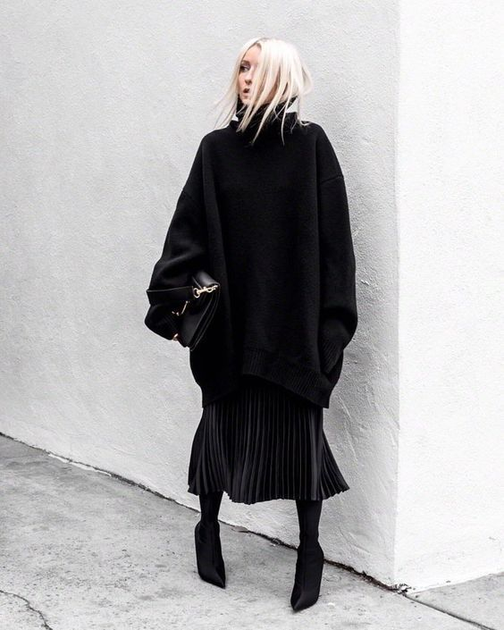 an oversized black sweater, a black pleated midi and sock boots plus a large black bag