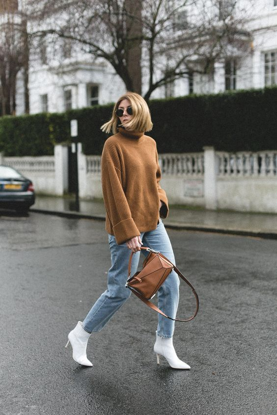 an oversized brown turtleneck sweater, blue jeans, white ankle booties and a brown geometric bag
