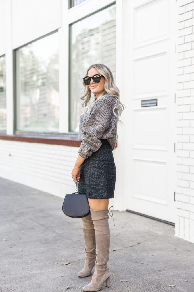 an oversized chunky knit grey sweater, a teal tweed mini skirt, grey suede tall boots and a black bag