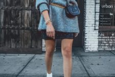 an oversized grey one shoulder cashmere sweater, a black leather mini skirt with studs, white snakle booties and a black waist bag