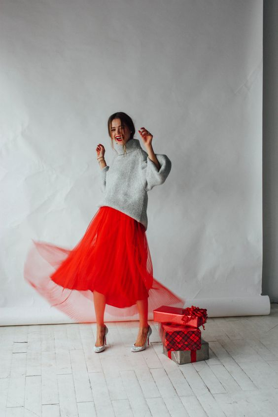 an oversized grey sweater, a red plaid pleated midi skirt and silver heels plus a red lipstick