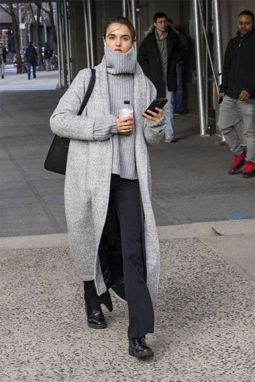 an oversized grey sweater, black striped pants, black boots, a grey midi coat and a black bag