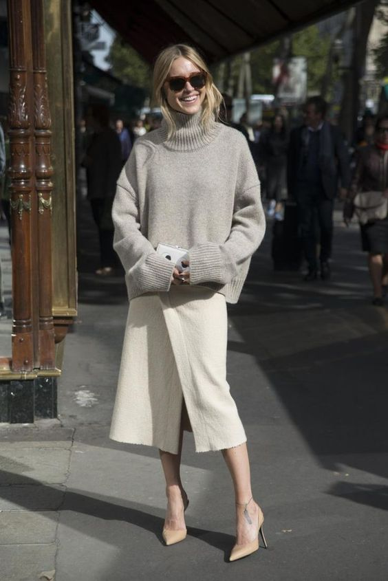 an oversized grey turtleneck sweater, an ivory wrap midi skirt, tan shoes and a white clutch for a minimalist look