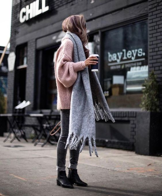 an oversized pink sweater, grey jeans, black booties, an oversized grey scarf for a cozy winter look