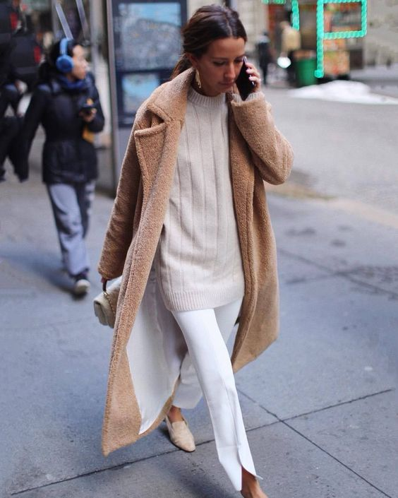 an oversized striped tan sweater, white pants, tan shoes and a brown faux fur coat plus a small white bag